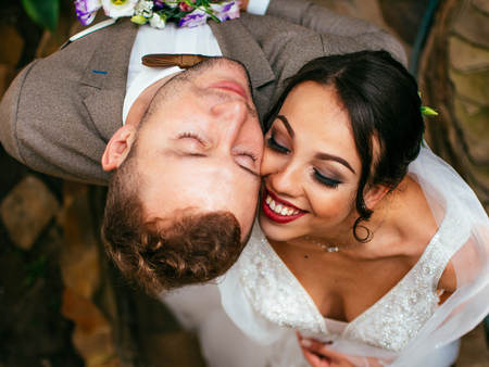 Wedding couple indoors is hugging each other. Beautiful model girl in white dress. Man in suit. Beauty bride with groom. Cute lady and handsome guy