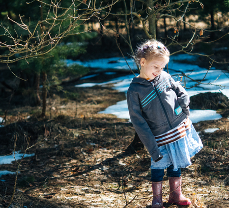Little village girl standing in the spring forest and smiling. Archivio Fotografico