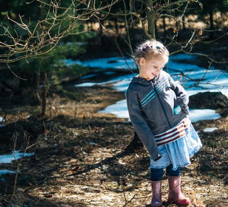 Little village girl standing in the spring forest and smiling. Reklamní fotografie