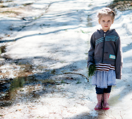 Serious little girl standing on the ice. Spring warm day Standard-Bild - 117770351