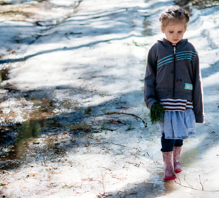 Serious little girl standing on the ice. Spring warm day Archivio Fotografico