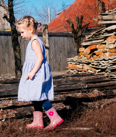 Little girl in early spring in the village. Archivio Fotografico