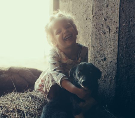 Little girl with a dog in a barn on straw.