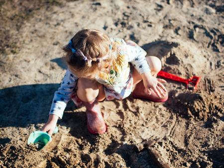 child playing with sand, day in the village