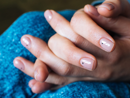 Womens hands are locked in the lock. Nude manicure.