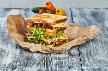 ham and cheese sandwich on toasted toast bread on a wooden background with craft paper, fresh ripe vegetables
