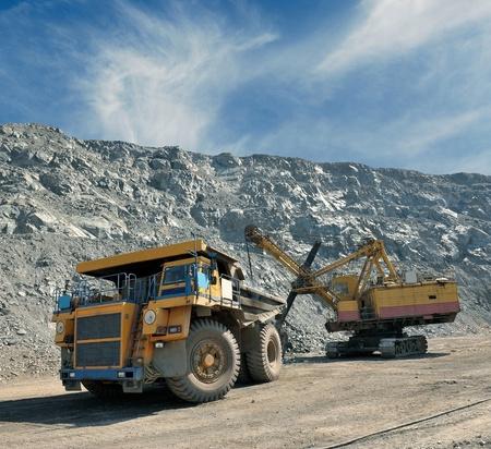 Loading of iron ore on very big dump-body truck 免版税图像