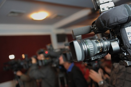 Videocamera and journalists at press conference 免版税图像