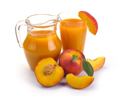 peach juice in a jug and a glass of fruit photo