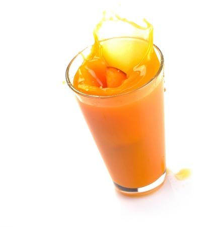 jus orange glazen: perziksap splash op een witte achtergrond