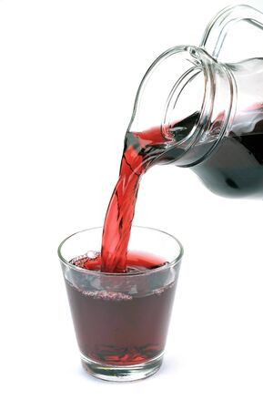 cherry juice is poured from a jug into a glass Stock Photo - 13503874