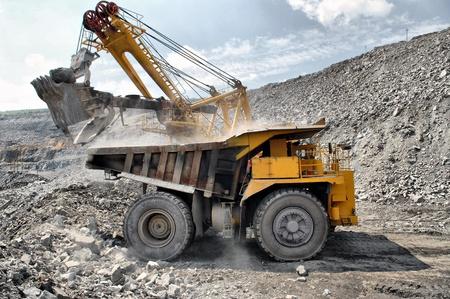 iron ore: Loading of iron ore on very big dump-body truck Stock Photo