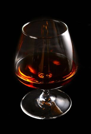 Glass of brandy over black background photo