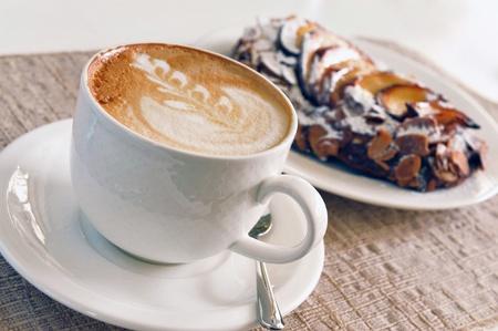 Feingeb�ck: Cappuccino und Kuchen auf dem Tisch Lizenzfreie Bilder