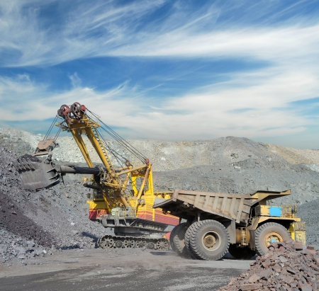 Loading of iron ore on very big dump-body truck photo