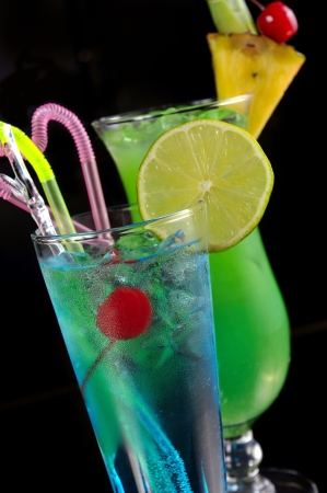 green cocktail with pineapple and blue cocktail with ice and lime on black with reflection Stock Photo - 13636100