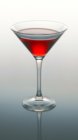Martini glass with red coctail on gray background photo