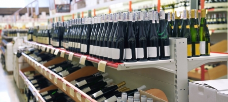 wine stocks: Red and white wine in bottles in wine shop Stock Photo