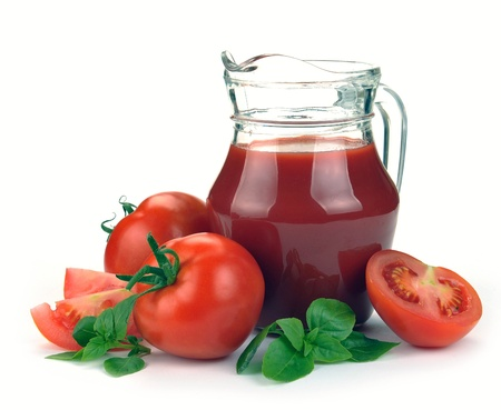 Jug, glass of tomato juice and fruits with green leaves on white photo