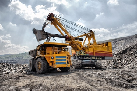 La carga de mineral de hierro en el camión volcado muy grande HDR-cuerpo Foto de archivo