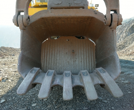excavator bucket in the career of iron ore photo