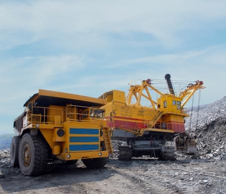Loading of iron ore on very big dump-body truck Stock Photo - 13782381