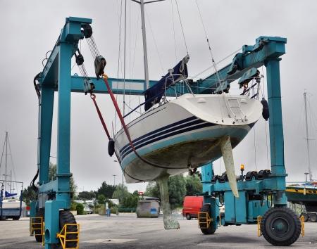 handling: Crane lifting boats at harbor Stock Photo