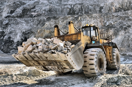 mover: Wheel loader machine unloading rocks in the open-mine of iron ore Stock Photo