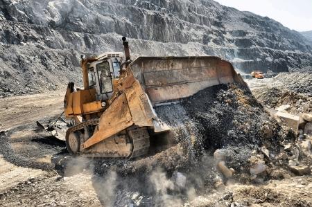 Wheel loader machine unloading rocks in the open-mine of iron ore 免版税图像
