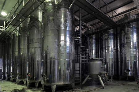 Stainless steel wine vats in a row inside the winery. photo