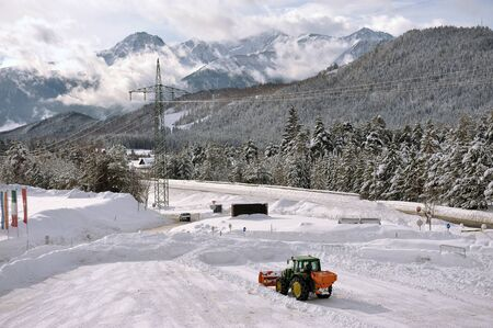 clearing snow from the parking lot for cars at the ski resort photo