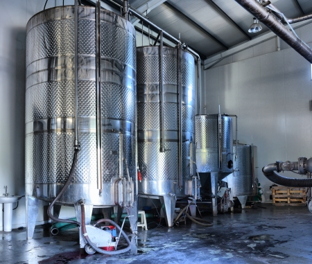 Stainless steel wine vats in a row inside the winery Stock Photo