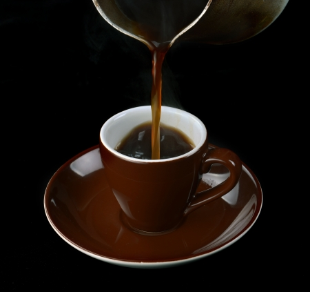 cezve: pouring coffee in a cup of Cezve