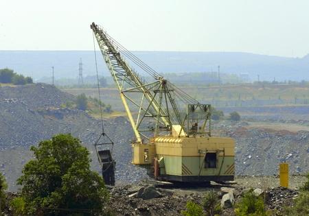 dumps: walking excavator digs waste rock dumps at