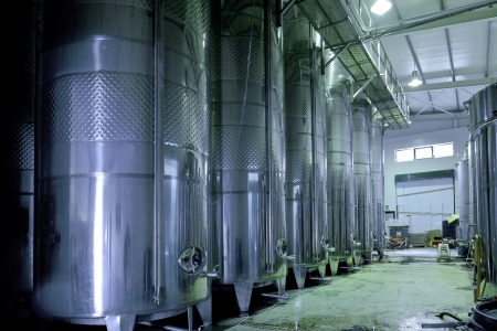 Stainless steel wine vats in a row inside the winery 免版税图像