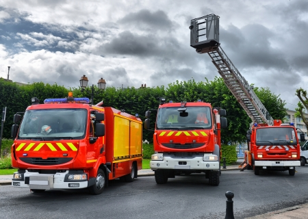 three fire trucks parked in the bay with all of the fire fighting equipment and gear ready to go Stock Photo