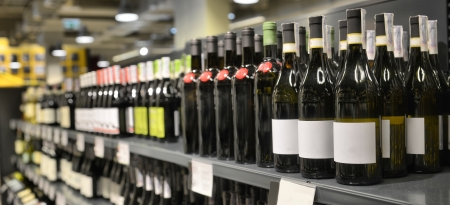 Red and white wine in bottles in wine shop 免版税图像