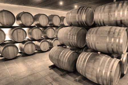 Casks in wine cellar and bottle 免版税图像