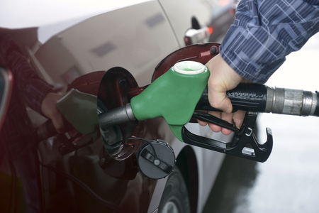 man hand refilling up gas tank of the car with green eco fuel on a filling station photo