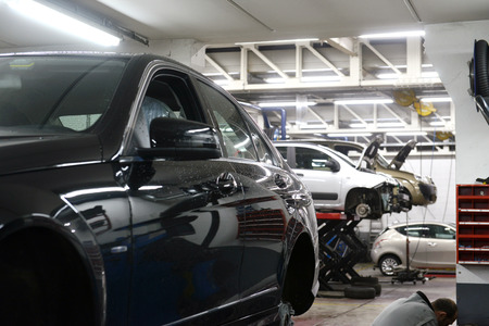 dirty car: car in garage with special equipment prepared for repair Editorial