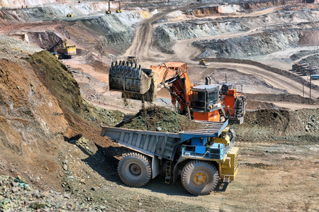 mining: Loading of iron ore on very big dump-body truck Stock Photo