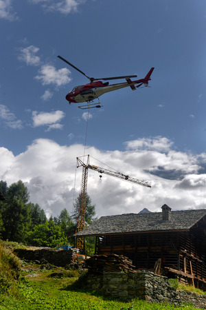 uplift: helicopter carries cargo in the Alps at a construction site