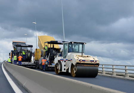job site: France - July 13 2012: On the job site - laying asphalt on the bridge of workers and road construction machinery on July 13 2012, France