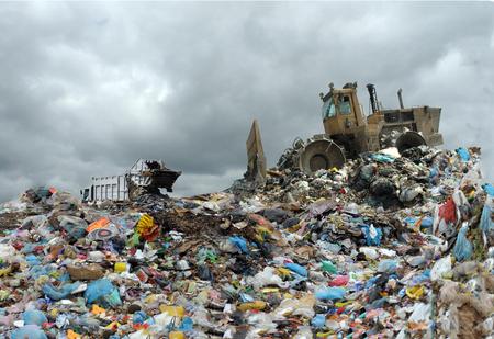 ごみ収集車がダンプでコンテナーからゴミをアンロードします。 写真素材