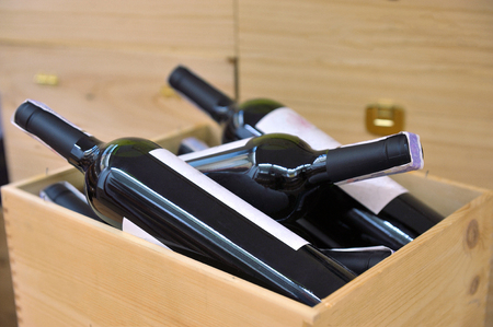 vintages: Bottle of red and white wine in wooden box in wine shop Stock Photo