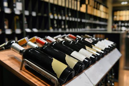 vintages: rows of  wine bottles for sale on shelf at food supermarket