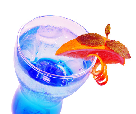 A single-colored transparent cocktail, refreshing shining in a low blue glass with crushed ice frappe and semicircle of a slice of lemon. Side view Isolated white background.