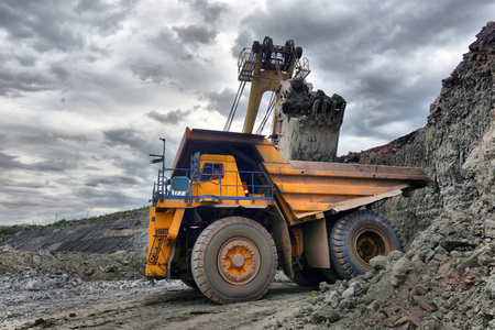 Large quarry dump truck. Loading the rock in the dumper. Loading coal into body work truck. Mining truck mining machinery, to transport coal from open-pit Standard-Bild