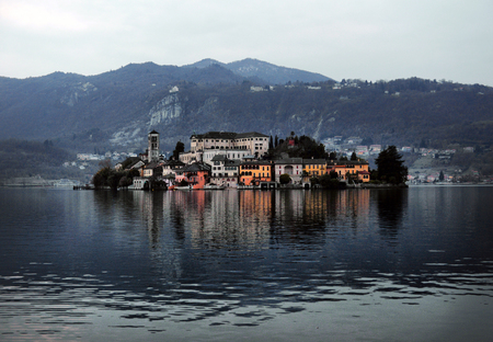 Orta Lake landscape. Orta San Giulio village, island Isola S.Giulio and Alps mountains view, Piedmont, Italy, Europe.