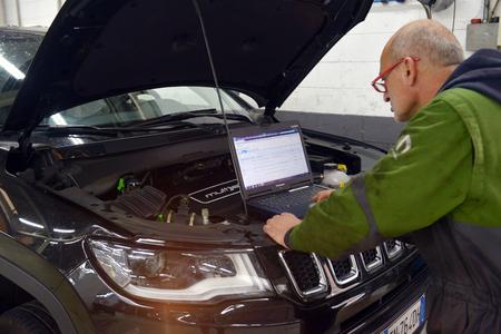 Italy, Desio, 26 october, 2018, Car technician repairing car in workshop service station,  Italy, Desio, 26 october, 2018